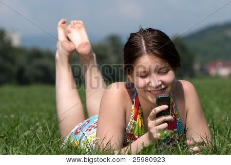 Girl speaks by mobile phone against summer green nature