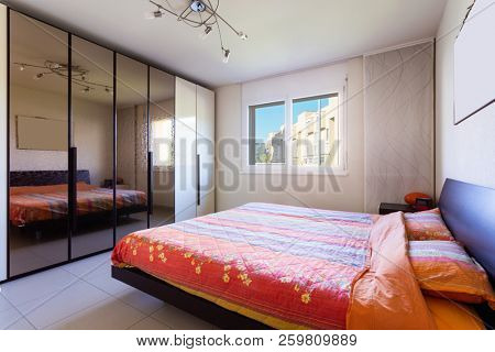 Bedroom with window with blue sky. Nobody inside