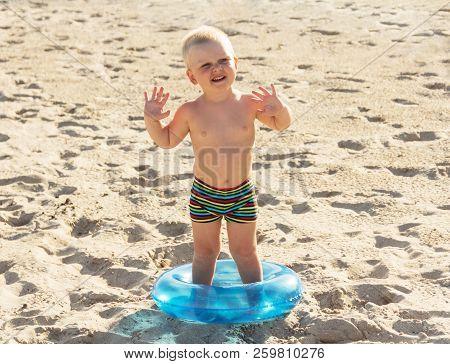 Joyful Happy Boy On A Sunny Beach With A Circle