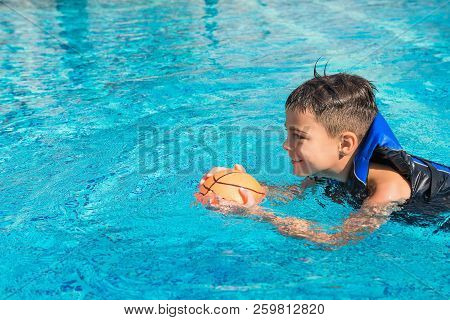 Happy Kid In Vest At Swimming Pool With Ball. Chilhood, Leisure, Swimming Theme