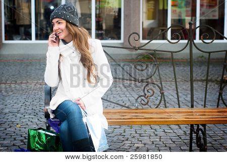 Young smiling Woman sitting on Berm telefonieren mit Handy