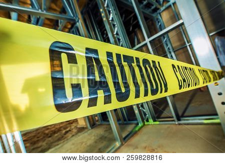 Yellow Caution Tape Closed Construction Zone. Dangerous Area Within Industrial Area.
