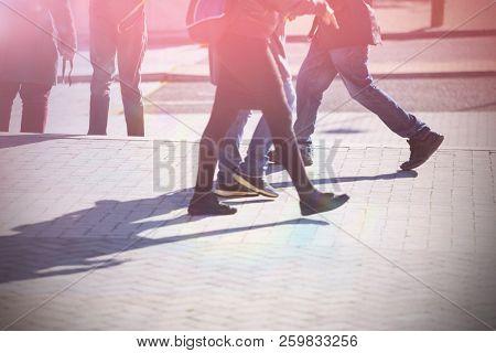 Low section of people walking on sidewalk in city