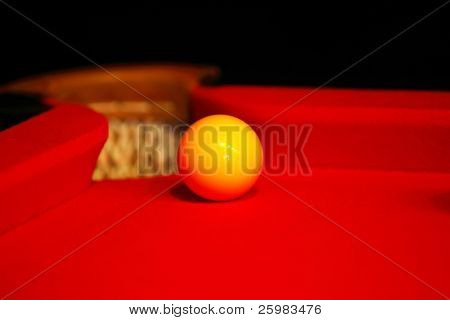 Billiard yellow ball on a red cloth