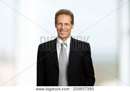 Cheerful Mature Businessman, Portrait. Middle-aged Man In Suit And Tie Smiling And Looking Aside. Po