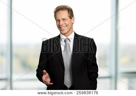 Welcoming Businessman Looking Happy. Smiling Businessman With Arm Out. Executive With Welcoming Gest