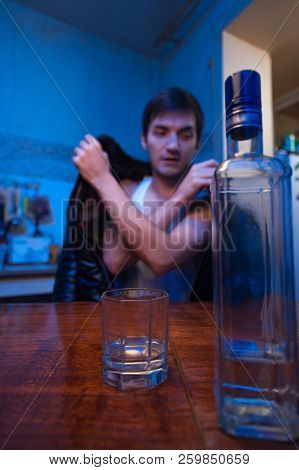 Young caucasian man drinking alcohol at home. Drunken male adult sitting at the table with glass and bottle. Alcohol abuse. poster