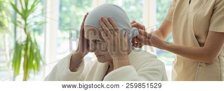 Panorama Of Caregiver Putting Scarf On Elderly Woman's Head During Chemotherapy