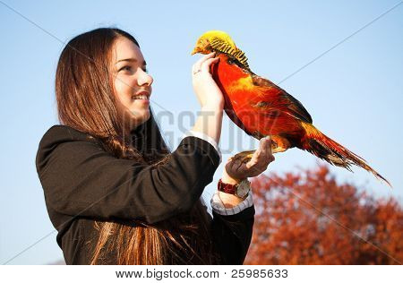 The happy teen with a pheasant on hand poster