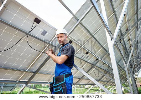 Young Engineer Technician Making Electrical Wiring Standing Inside High Exterior Solar Panel Photo V
