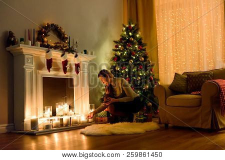 Nice Woman In A Cosily Lighted Christmas Decorated Room Fixing Candles On A Fireplace. Christmas Roo