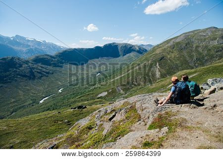 Couple Of Hikers Sitting On Besseggen Ridge In Jotunheimen National Park, Norway