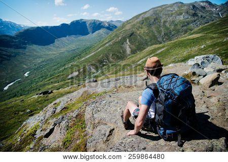 Traveler With Backpack Resting On Besseggen Ridge In Jotunheimen National Park, Norway