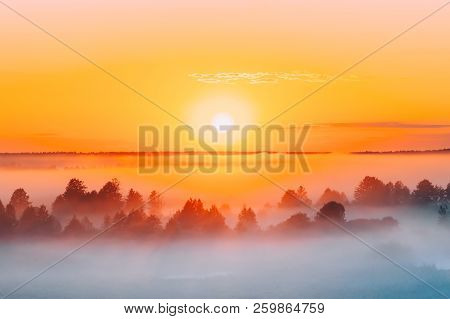 Sunrise Over Misty Landscape. Scenic View Of Foggy Morning Sky With Rising Sun Above Misty Forest. M