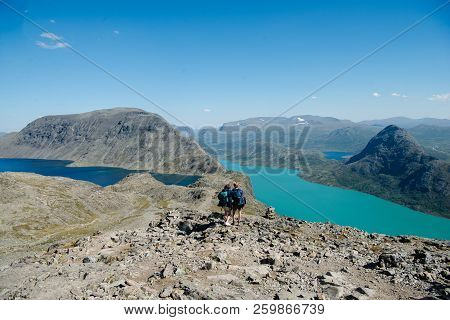 Couple Of Hikers Walking On Besseggen Ridge Over Gjende Lake In Jotunheimen National Park, Norway