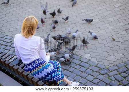 Woman Tourist Or Citizen Toss Crumbs For Pigeons. Girl Blonde Woman Relaxing City Square And Feeding