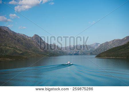 Boat Floating On Calm Blue Water Of Gjende Lake, Besseggen Ridge, Jotunheimen National Park, Norway