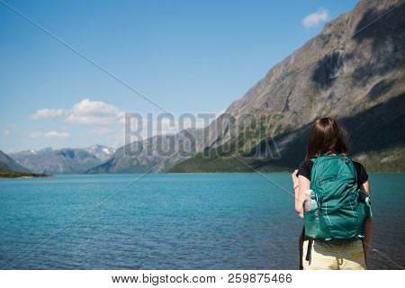 Rear View Of Young Woman With Backpack Looking At Majestic Gjende Lake, Besseggen Ridge, Jotunheimen