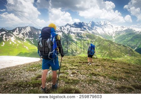 Hiking Trail With Tourists In Mountain Range. Trekking In Mountains. Two Hikers Hike On Snowy Highla