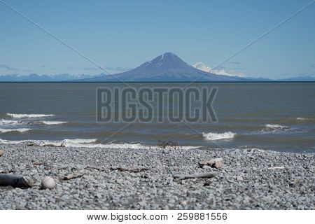 Augustine Island, An Active Volcano As Seen From A Beach Covered In Rocks And Driftwood In Katmai Na