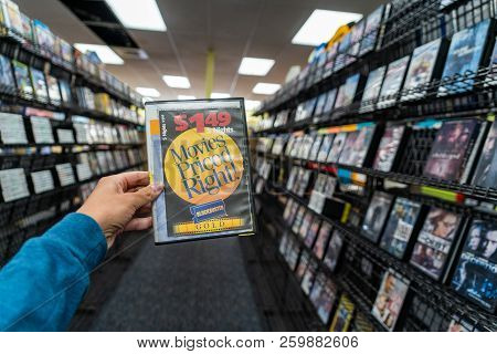 August 12 2018 - Fairbanks, Ak: A Women Customer Hand Holds Out A Dvd Movie For Sale Inside Of One O
