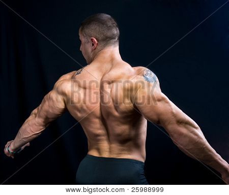 A perfect muscular man posing artistic, back double biceps