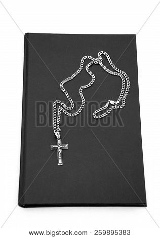Silver Cross Wth Chain On The Book With Black Cover Over White Background