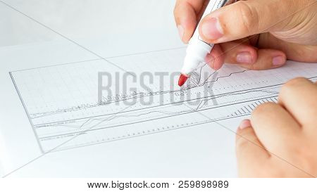 Closeup Photo Of Businessman Holding Red Marker Analyzing Stock Sales Rates And Financial Data