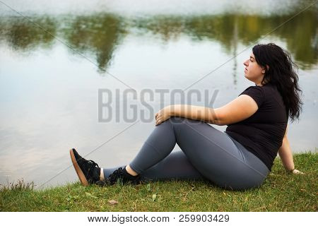Body Positive, Yoga, Meditation, Tranquility, Relax. Overweight Woman Sitting Near Lake Contemplatin