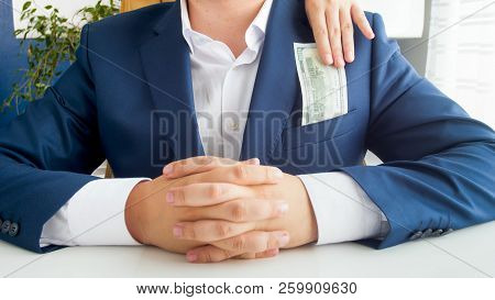 Closeup Image Of Wife Taking Money From Her Husband's Jacket Pocket