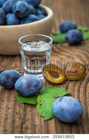 Fresh Blue Plums And Plum Brandy On Wood Table Background. Sweet Autumn Fruit. Delicious And Healthy
