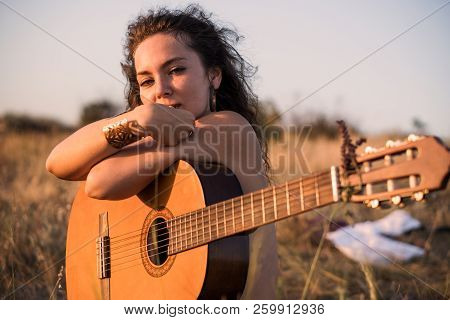 Naked Contemplative Brunette Girl Sitting With Guitar In The Field With Taked Off Clothes On Backgro