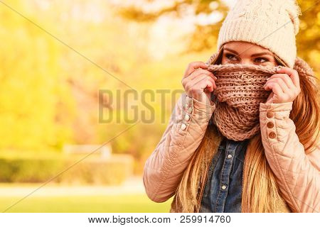 Young Woman Walking In Autumnal Park, Hiding Her Face With Warm Woolen Scarf. Beautiful Sunny Autumn