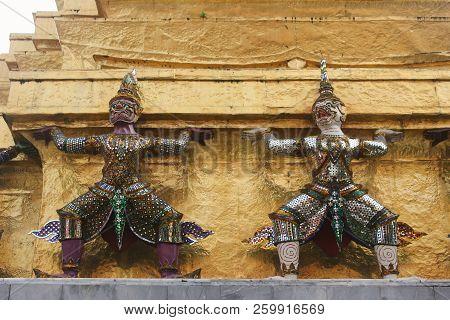 Close up of two demon statues, or demon guardians, holding Golden Chedi prang at Wat Phra Kaew temple. Bangkok, Thailand poster