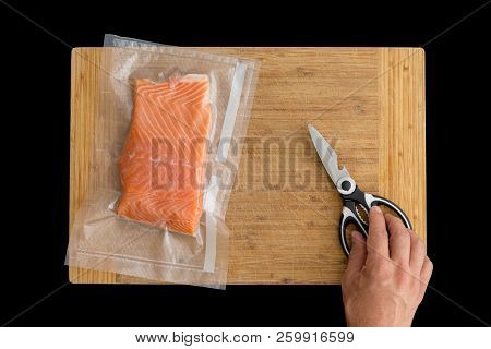 Vacuum Packed Fillet Of Fresh Atlantic Salmon Ready For Freezing Or Sous-vide Cooking On A Wooden Bo