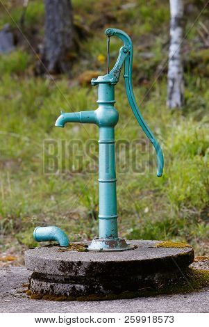 Vintage Green Hand Operated Water Pump Above Its Well.