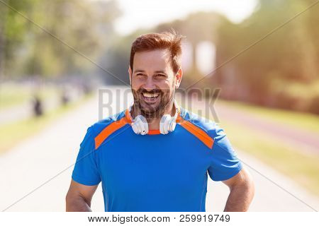 Satisfied Handsome Man Running In Park. Urban Morning Jogging