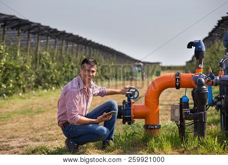 Handsome Engineer With Tablet Squatting Beside Pipe System For Irrigation In Modern Apple Orchard Wi
