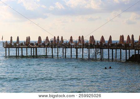 The Pier Near Beach. Wooden Pier With Sunbeds.