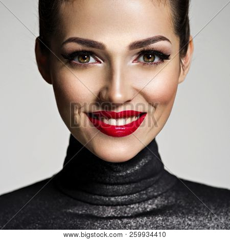 Beautiful young smiling woman with red lipstick. Glamour fashion model with bright gloss make-up  posing at studio. Young woman with positive face expression