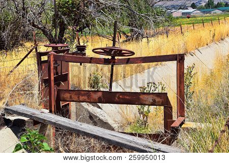 Winch Of Pair Of Rusty Antique Irrigation Ditch Gates Against Sky With Tall Grass In Heber City, Uta