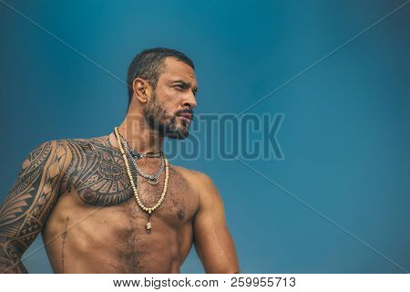 Muscular Latin Lover. Latin Man With Muscular Body Looks Seriously. Handsome Brutal Man On Blue Sky