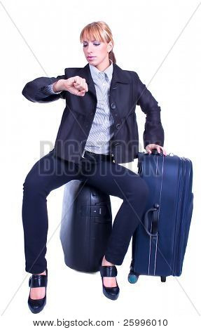 Young businesswoman sits on black suitcase and waiting for somebody, isolated on white