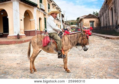 TRINIDAD, CUBA - JANUARY 14: Old men with cigar and donkey for rent in Trinidad. Working in tourism is the only way Cuban people can earn a decent income, on January 14, 2010 in Trinidad, Cuba.