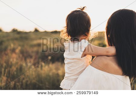 Cropped Rear View Of Caucasian Brunette Mother And Child Daughter Embrace Each Other On Meadow Sunse