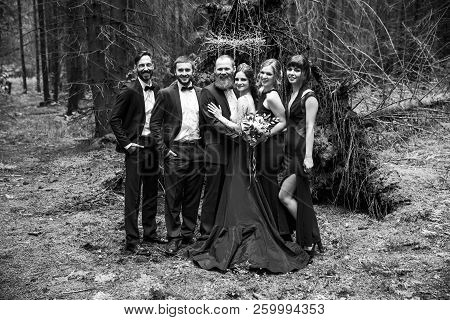 Black-and-white Photo In Retro Style.the Couple And The Witnesses In The Background Of A Hut In The