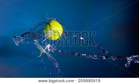 Tennis Ball And Splashes Of Water On A Blue Background.