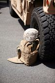 us military flack jacket and helmet lay against a h1 humvee poster