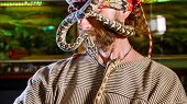 Snake on the man's face. Portrait of mad bearded hipster with snakes cawling on his head and face. Terrible video with snakes in role of domestic pets poster