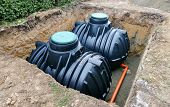 Two plastic underground storage tanks placed below ground for harvesting a rainwater. poster